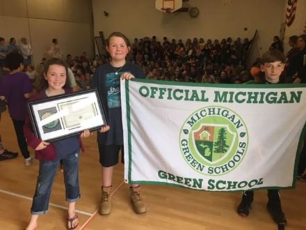 Maplewood School students holding Michigan Green School framed certification and flag at a ceremony